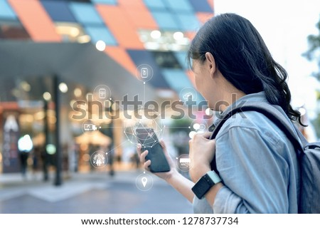Attractive smart asian traveller woman use her smartphone to booking hotel in ecommerce website on omni channel platform. She can do every steps on only one mobile.