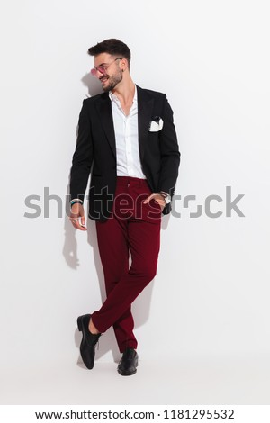 attractive smart casual man looks to side and smiles while leaning against a white wall, looking relaxed, full body picture