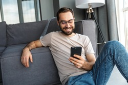 Attractive smart young man sitting on a floor in the living room, using mobile phone