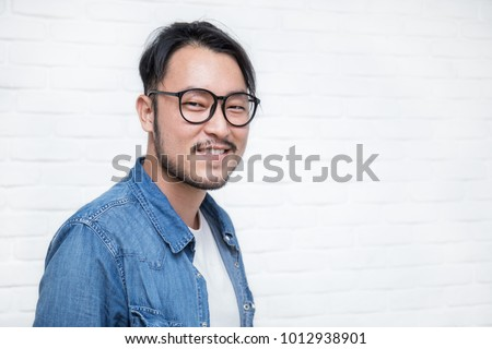 Attractive smile handsome positive asian nerd man. Close up portrait of asian nerdy man wearing eye glasses over white background.