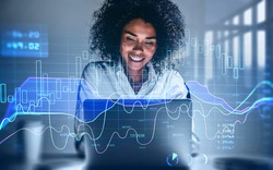 Attractive smiling African American business woman or stock trader analyzing stock graph chart using laptop, Portrait front view businesswoman.