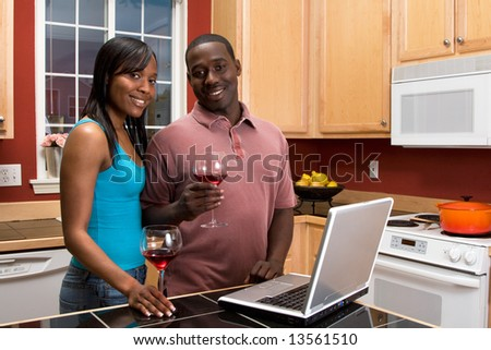 Attractive smiling African American couple standing in a kitchen, holding wine glasses, while using a laptop. Horizontally framed shot with the man and woman looking at the camera.