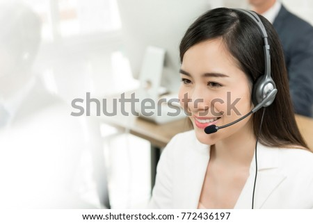 Attractive smiling Asian woman call center staff with headset offering customer service assistance to business or personal client on direct information helpline