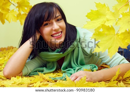 attractive smiling brunette woman lying in yellow fallen leaves, wearing green scarf