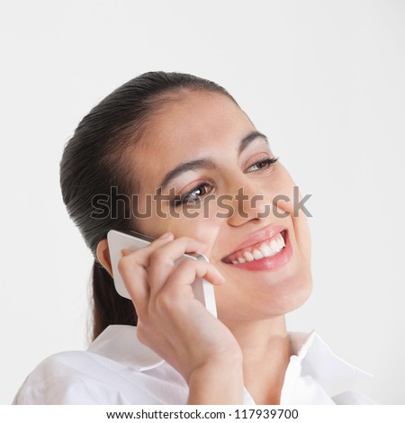 Attractive smiling business woman using her smartphone to make a call