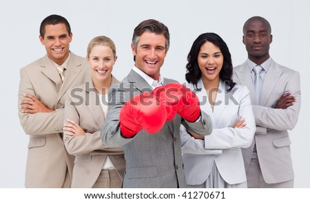 Attractive smiling businessman with boxing gloves leading his team