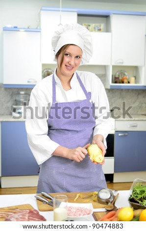 Attractive smiling chief cook preparing food, peeling potatoes