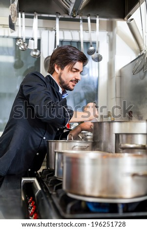 Attractive smiling cook or chef stirring a huge stainless steel pot of stew or casserole on a hob in a commercial kitchen at a restaurant or hotel