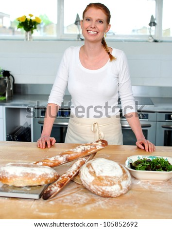 Attractive smiling female cook posing in kitchen