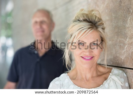 Attractive smiling friendly middle-aged woman with her long blond hair held up loosely around her face standing against a receding wall looking at the camera