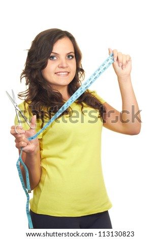 Attractive smiling girl in a yellow shirt holding a scissors in the right hand and in the left hand holds a centimeter. Isolated on white background