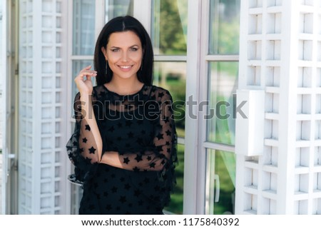 Attractive smiling girl meets her guests on the porch, widely openly smiles to friends, the concept of people, relationships, smile, greeting. #1175840392