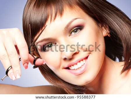 Attractive smiling girl with scissors, cutting her hair