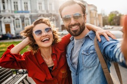 attractive smiling man and woman traveling together, stylish couple in love taking selfie photos on phone on romantic trip, sunny autumn city, wearing shirt, sunglasses, travelers having fun