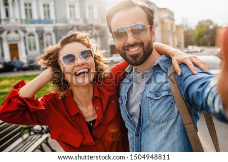 attractive smiling man and woman traveling together, stylish couple in love taking selfie photos on phone on romantic trip, sunny autumn city, wearing shirt, sunglasses, travelers having fun Stockfoto ©