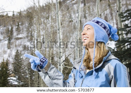 Attractive smiling mid adult Caucasian blond woman wearing blue ski clothing smiling and pointing.