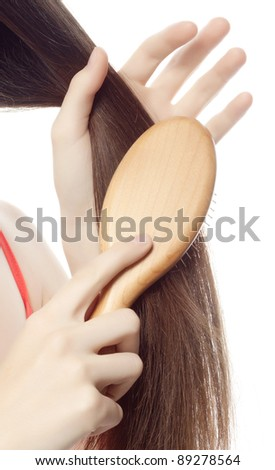 attractive smiling woman brushing her hair on white background
