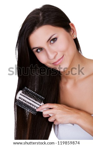 Attractive smiling woman brushing her long straight brunette hair isolated on white