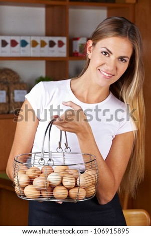 Attractive smiling woman carrying basket full of free range eggs