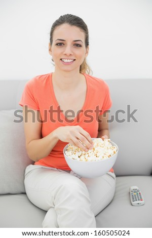 Attractive smiling woman eating popcorn while watching television ans sitting on couch