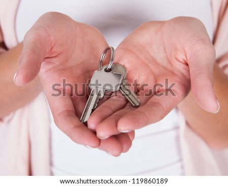 Attractive smiling woman holding up a set of keys belonging to her house or car in her hand isolated on white - stock photo