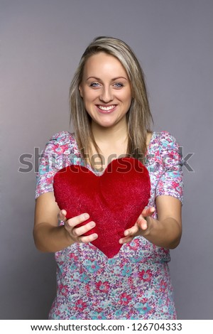 attractive smiling woman on gray background holding a red heart