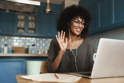 Attractive smiling young african woman on a video call with colleagues, sitting on a kitchen with laptop computer, waving