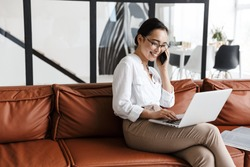Attractive smiling young asian business woman relaxing on a leather couch at home, working on laptop computer, talking on mobile phone