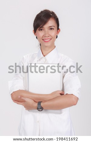 Attractive smiling young business woman casual holding laptop computer, isolated on white background