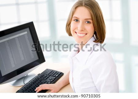 Attractive smiling young business woman using computer at work desk