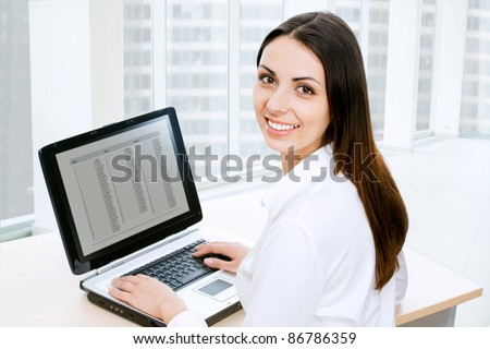 Attractive smiling young business woman using laptop at work desk