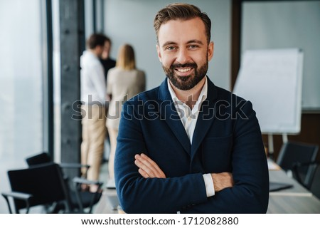 Attractive smiling young confident businessman in formal wear standing in the office with his colleagues on a background, arms folded