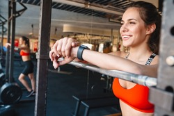 Attractive smiling young fit sportswoman standing in the gym, resting after exercises, leaning on a rail