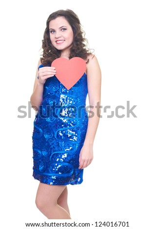 Attractive smiling young woman in a blue brilliant dress holding red heart. Isolated on white background