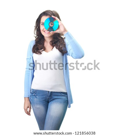 Attractive smiling young woman in a blue shirt holding disk near her left eye. Isolated on white background