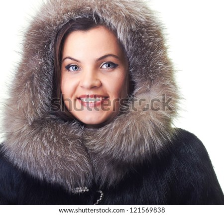 Attractive smiling young woman in a fur coat and a fur hood. Isolated on white background