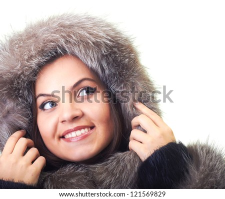 Attractive smiling young woman in a fur coat and a fur hood looking at the upper-left corner. Isolated on white background