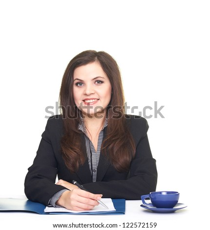 Attractive smiling young woman in black jacket sitting at a table and sign documents. Isolated on white background