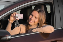 Attractive smiling young woman proudly showing her driving license out of car window. Woman has got driving license and feels very happy and excited. Ready to drive