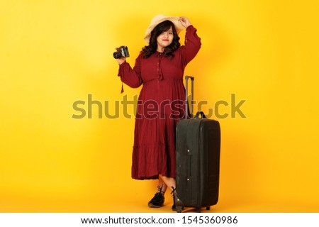 Attractive south asian traveler woman in deep red gown dress, hat posed at studio on yellow background with suitcase amd old vintage photo camera.