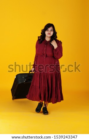 Attractive south asian traveler woman in deep red gown dress posed at studio on yellow background with suitcase.