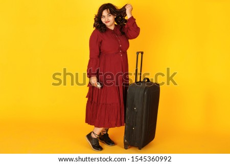 Attractive south asian traveler woman in deep red gown dress posed at studio on yellow background with suitcase and credit cards.