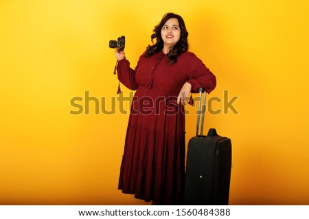 Attractive south asian traveler woman in deep red gown dress posed at studio on yellow background with suitcase and old vintage photo camera.