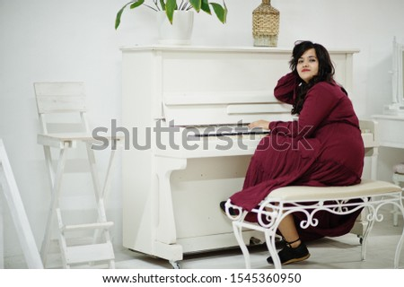 Attractive south asian woman in deep red gown dress posed at room and play on piano.