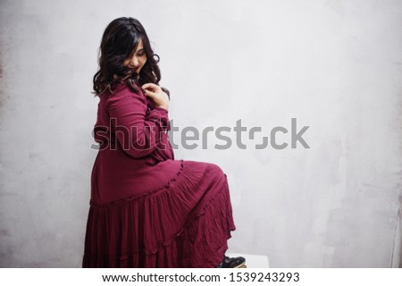 Attractive south asian woman in deep red gown dress posed at studio against white wall.