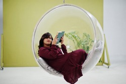 Attractive south asian woman in deep red gown dress posed at studio and read a book at rocking chair ball.