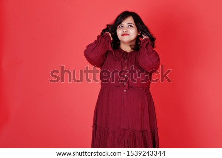 Attractive south asian woman in deep red gown dress posed at studio on pink background.