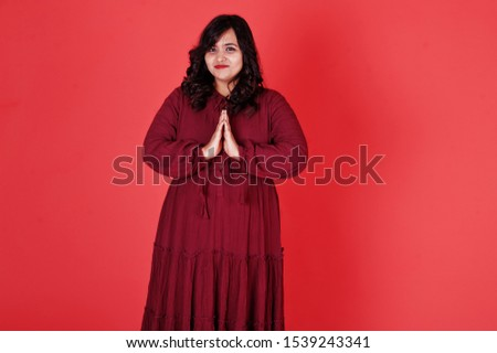 Attractive south asian woman in deep red gown dress posed at studio on pink background and show namaste sign by hands.