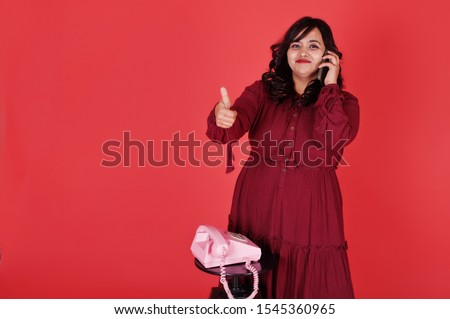 Attractive south asian woman in deep red gown dress posed at studio on pink background and use old vintage telephone and show thumb up.