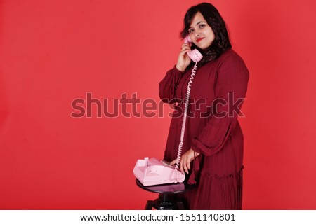 Attractive south asian woman in deep red gown dress posed at studio on pink background and use old vintage telephone.